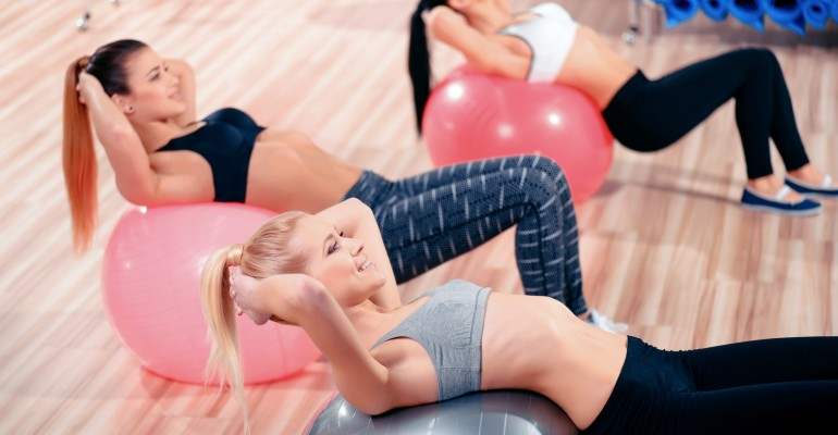 Taking the fitness journey together. Three beautiful young women in sports clothing exercising together on fit balls at the gym and smiling